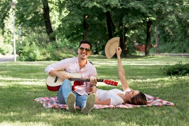 スマイリー男が公園でギターを弾く 無料写真