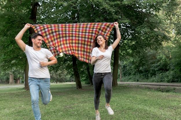 愛情のあるカップルの自然の中で毛布を実行しています。 無料写真