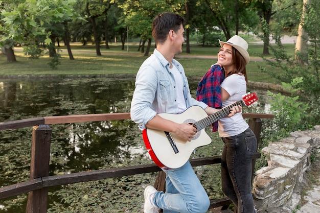 橋でお互いを見ている若いカップル 無料写真