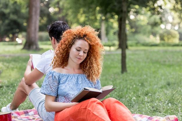 赤い髪の女性、ピクニック毛布の上に横たわると本を読んで 無料写真