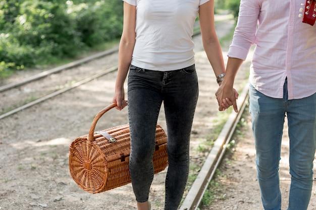 手を繋いでいると鉄道の上を歩く若いカップル 無料写真