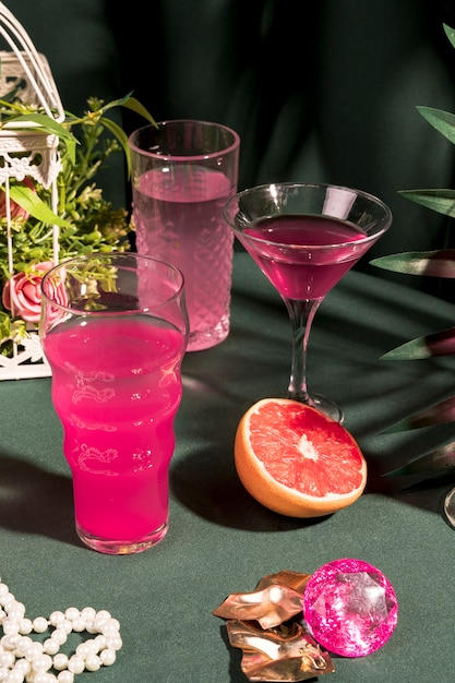 テーブルの上のガーリーなアイテムの横にあるピンクの飲み物 無料写真