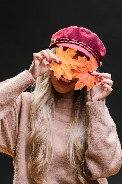 Стильная женщина прячется за сухими кленовыми листьями на черном фоне Бесплатные Фотографии