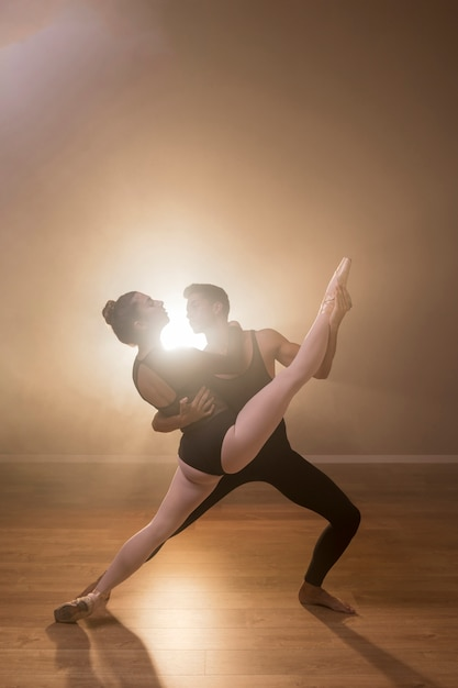 フルショットのバレリーナが男性ダンサーによって開催されています 無料写真