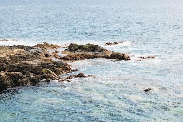 岩の多い海岸でビューの上の波状の水 無料写真