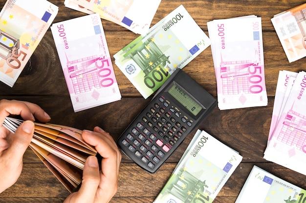 電卓でお金を数える平面図男 無料写真