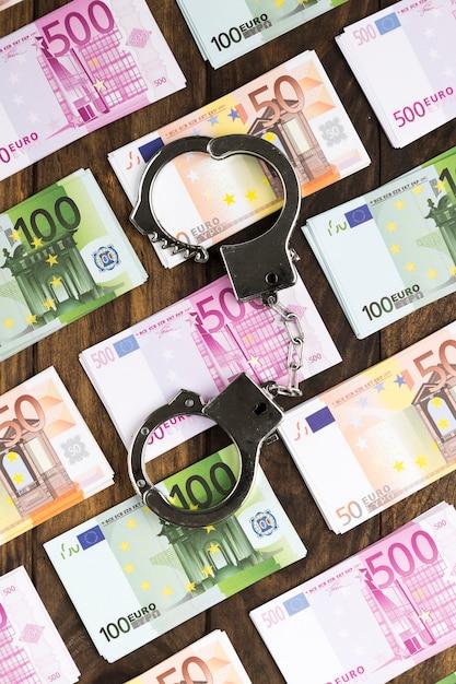 手錠と木製のテーブルの上の平らなレイアウト紙幣 無料写真