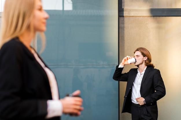 ビジネスの男性が外でコーヒーを飲む 無料写真