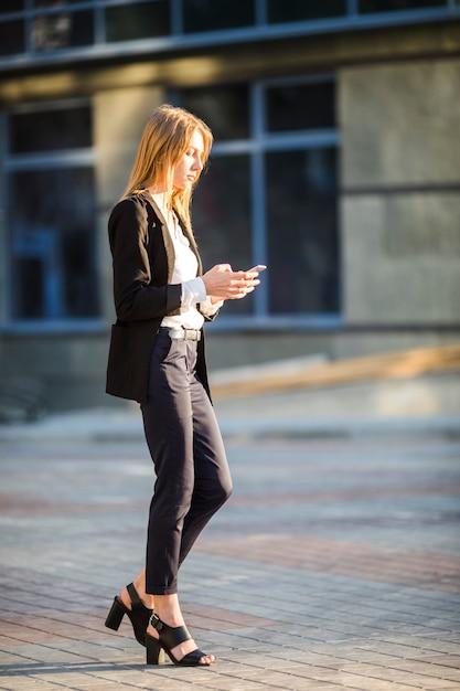横向きの女性が彼女の電話を使用しながら離れて歩いて 無料写真