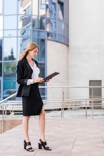 クリップボードを持つ若いビジネス女性 無料写真