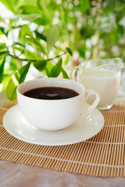 竹マットの上のミルクとコーヒーカップ 無料写真