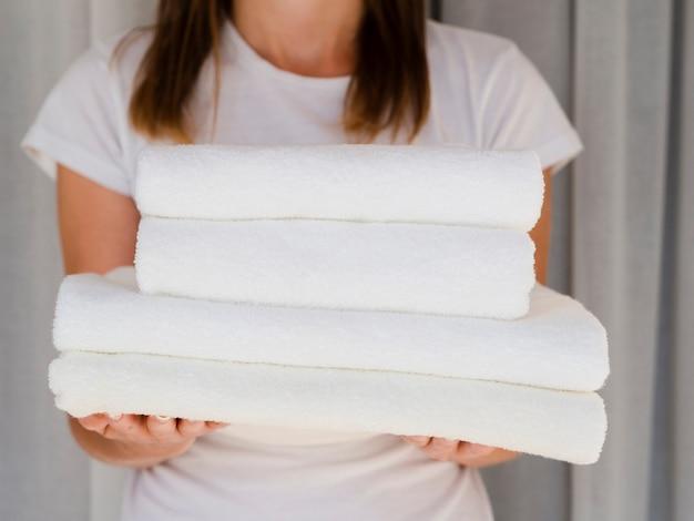 白い折られたきれいなタオルを保持しているクローズアップの女性 無料写真