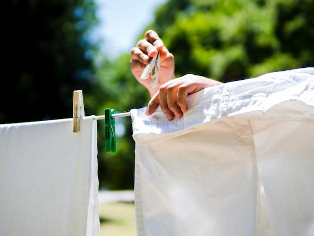 クローズアップ人のラインに白いジーンズをぶら下げ 無料写真