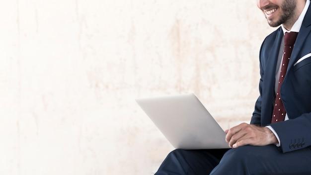Крупным планом мужчина в костюме работает на ноутбуке Бесплатные Фотографии