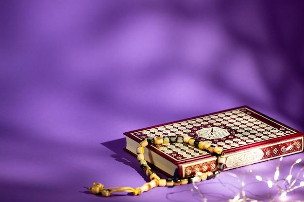 紫色の背景に閉じたコーラン 無料写真
