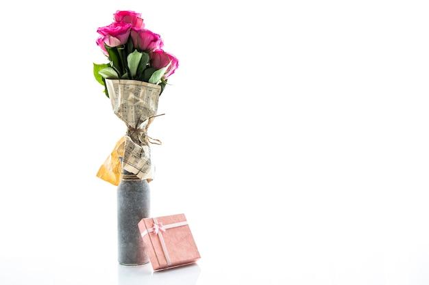 バラと小さな贈り物のミニマルな花瓶 無料写真
