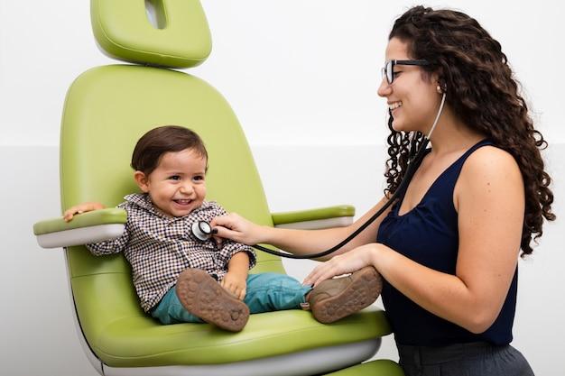 サイドビュー医師、子供を調べる 無料写真