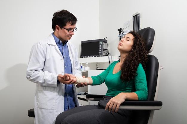 ミディアムショット医師が包帯の腕を調べる 無料写真