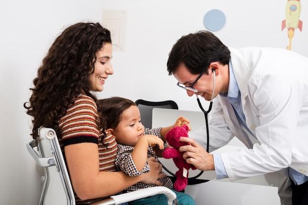 サイドビュー医師が男の赤ちゃんをチェック 無料写真