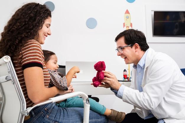 Доктор вид сбоку, играя с мальчиком Бесплатные Фотографии