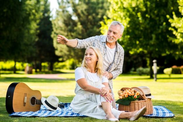 公園を離れて見ている高齢者のスマイリーカップル 無料写真