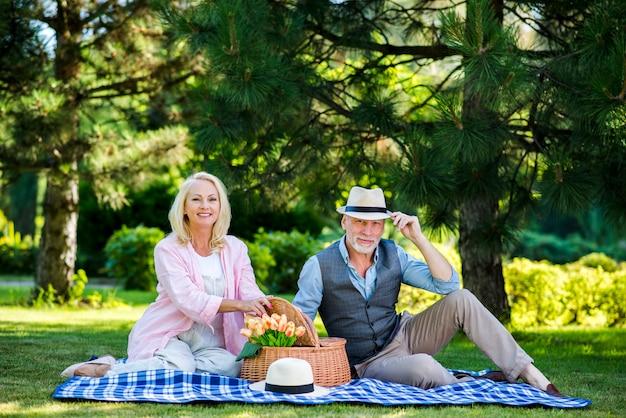 老夫婦のピクニックでカメラにポーズ 無料写真