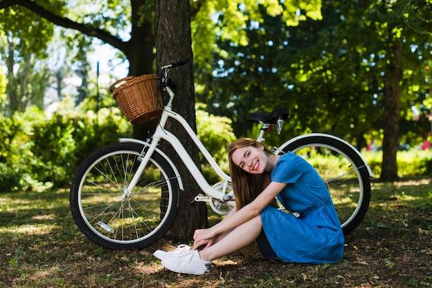 自転車の横にある森林の地面に座っている女性 無料写真