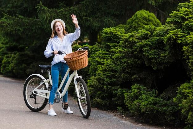 手を振っている自転車を持つ女性 無料写真