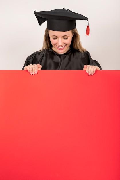 赤いプラカードモックアップを保持している美しい大学院 無料写真