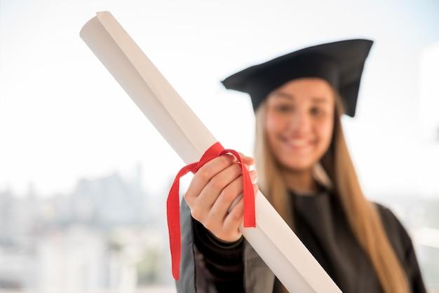 彼女の証明書のクローズアップを示す若い卒業生 無料写真