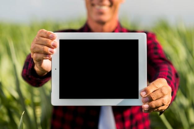 フィールドでタブレットを保持しているモックアップ男 無料写真