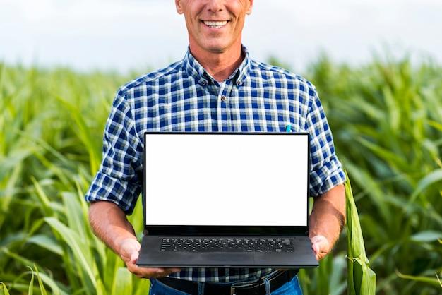 ノートパソコンのモックアップを持って中年男性 無料写真