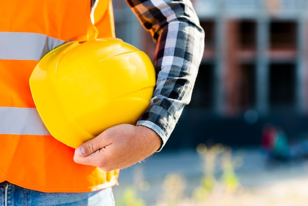 ヘルメットを保持しているクローズアップの建設労働者 無料写真