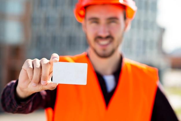 Средний выстрел портрет инженер-строитель держит визитную карточку Бесплатные Фотографии