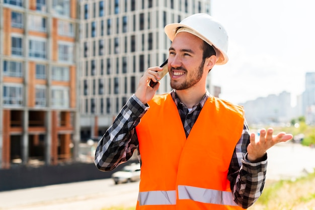 Средний снимок портрет инженер-строитель разговаривает по телефону Бесплатные Фотографии