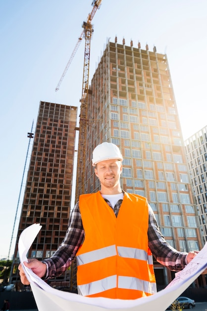 Средний снимок, инженер с низким углом зрения, смотрит на планы Бесплатные Фотографии