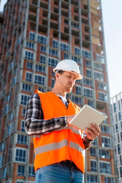 Средний снимок низкий угол зрения инженер-строитель глядя на планшет Бесплатные Фотографии
