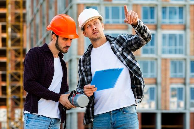 エンジニアと建築家のクリップボードを見てのミディアムショット 無料写真