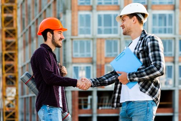 エンジニアと建築家の握手のミディアムショット 無料写真