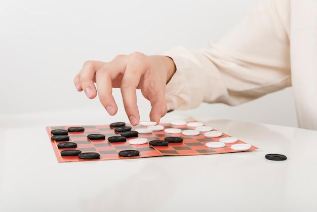 Крупным планом человек играет в шашки Бесплатные Фотографии