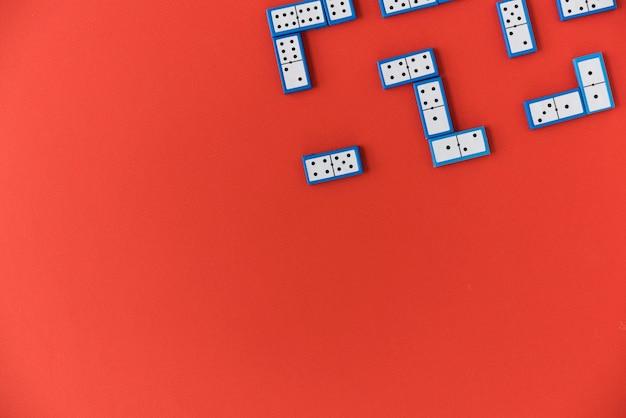 Вид сверху кусочки домино на красном фоне Бесплатные Фотографии