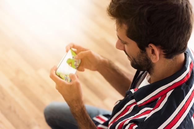 トップビューの男がモバイルゲームをプレイ 無料写真