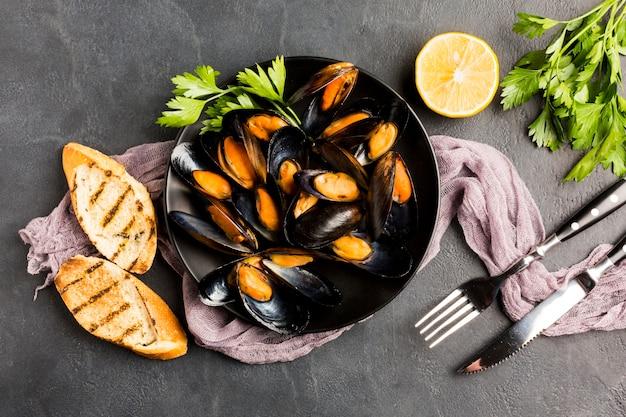 ムール貝とカトラリーの平らなプレート 無料写真