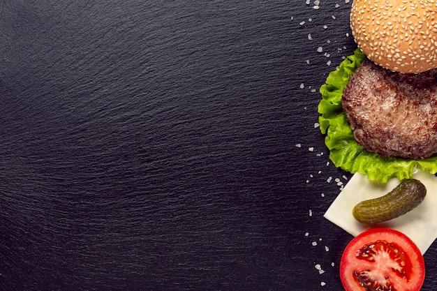 黒の背景にトップビューハンバーガーの食材 無料写真