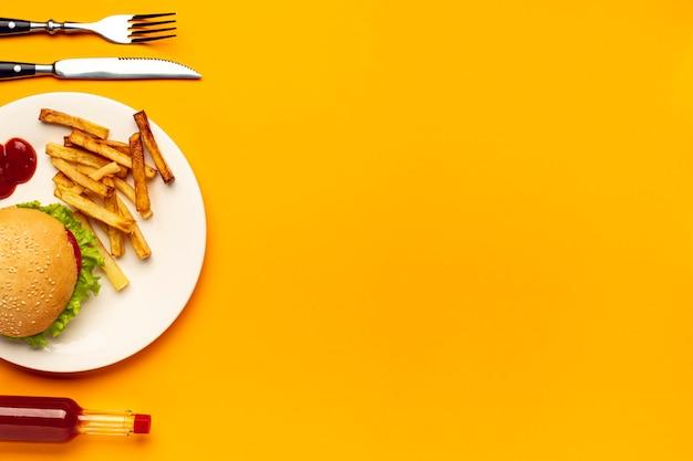 コピースペースを持つプレート上のハンバーガーとフライドポテト 無料写真