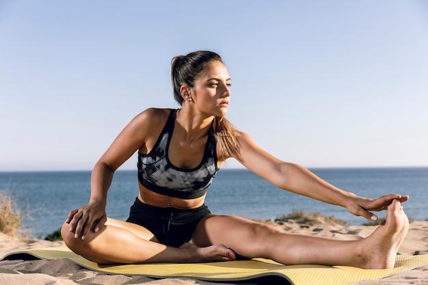 スポーティな女性がビーチでウォーミングアップ 無料写真
