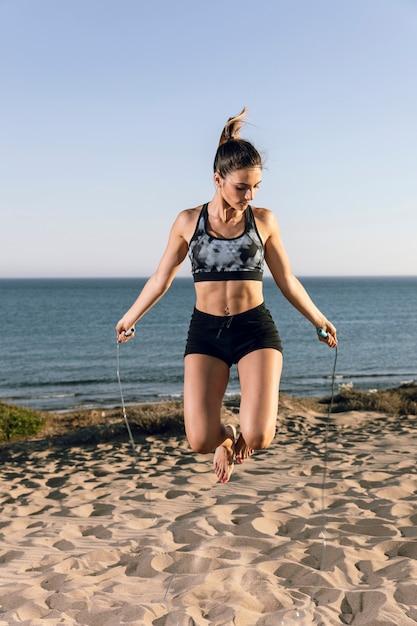 女性のビーチで縄跳び 無料写真