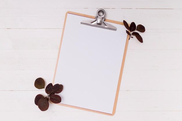 白いモックアップクリップボードと乾燥葉 無料写真