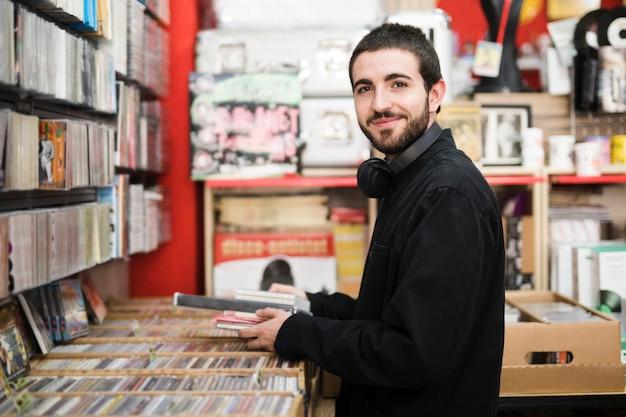 カメラ目線の音楽店で若い男のミディアムショット側面図 無料写真