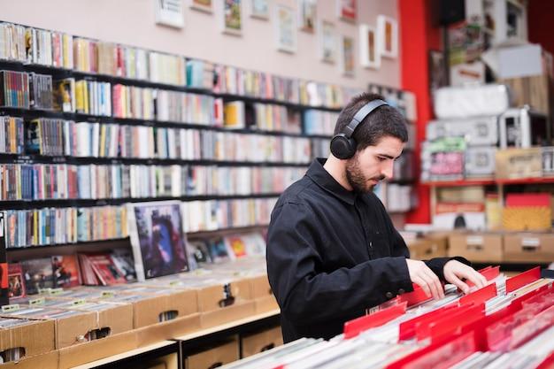 店でビニールを探している若い男のミディアムショット側面図 無料写真